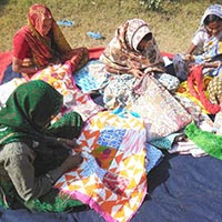 Group Members Doing Needle Work On Bed Cover